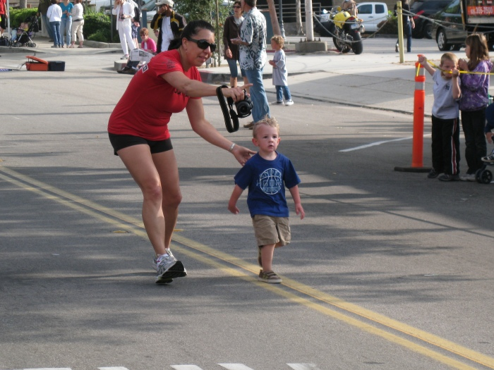 This Kid Kept On Going Back On the Road After Crossing The Tape At The Finish Line